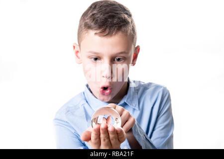Il ragazzo sembra totalmente sorpreso in una sfera di vetro e le speranze per un futuro buono Foto Stock