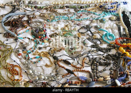 Gioielli. Una collezione di gioielli steso su un letto con un foglio bianco. Jewells. Gli oggetti di valore. Beni personali. Valore sentimentale. Pietre. Perle. Perline. Collane. Braccialetti. Un orologio da polso. Multi colorata. Assortimento.