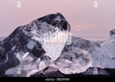 Sorprendente formazioni di ghiaccio sono organizzate da sera nubi accese da una copertura nuvolosa in tonalità rosse e gialle, il sole di setting è visibile - Posizione: Islanda, così Foto Stock