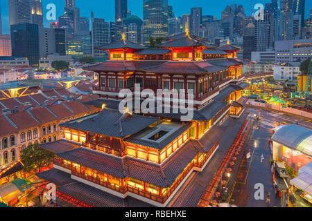 Singapore skyline della città con vista del Dente del Buddha reliquia tempio in notturna a Singapore.