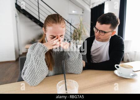 Riunione di una donna triste e un amico o un ragazzo cerca conforto per lei nel cafe Foto Stock