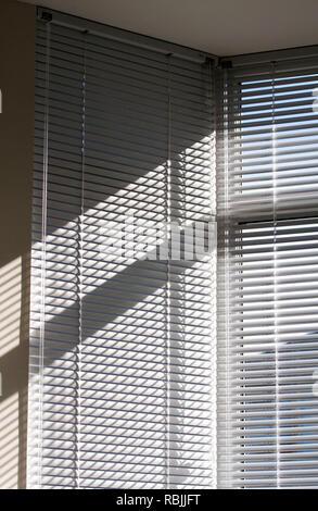 Luci e ombre attraverso le persiane della finestra