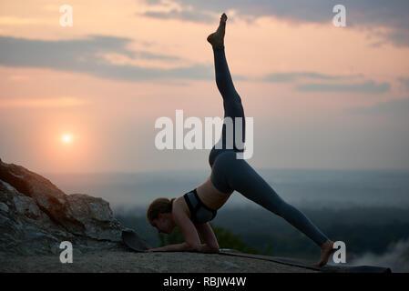 Silhouette di slim attraente ginnasta giovane donna facendo complicato aerobica esercizi di yoga all'aperto al tramonto in alta collina rocciosa su sfondo di beau Foto Stock