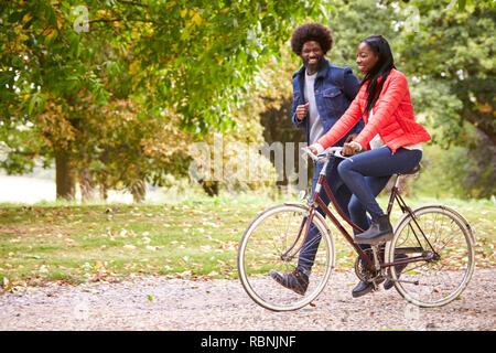 Uomo nero in esecuzione in un parco accanto alla sua fidanzata, chi è in sella a una moto, vista laterale