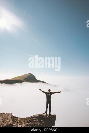 Escursionista uomo in piedi da sola sulla scogliera di montagna bordo sopra le nuvole le mani alzate viaggi avventura lifestyle vacanze attività outdoor emozioni di successo Foto Stock