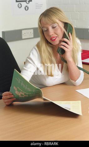 Giovane donna bionda parlando al telefono in ufficio Foto Stock