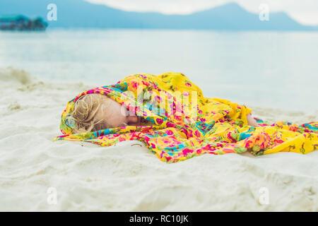 Adorable baby boy, dormendo sulla spiaggia, esausti dopo la giornata di divertimento in spiaggia. Foto Stock