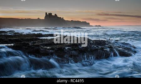 Impostazione di colori sun il cielo dietro il castello dove il mare del Nord crea il movimento e aggiungere la complessità per l'immagine Foto Stock