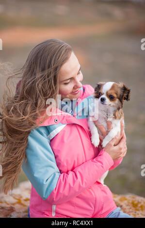 Bella giovane donna in tuta con capelli lunghi tenendo poco chihuahua cane freddo condizioni all'aperto Foto Stock