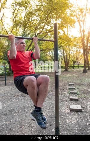 Una mezza età uomo Latino che esercitano in un parco Foto Stock