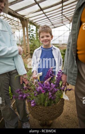 Ritratto di un ragazzo adolescente con sua sorella e il nonno all'interno di una serra. Foto Stock