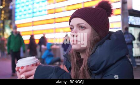 Giovane donna beve una tazza di caffè per le strade di New York Foto Stock