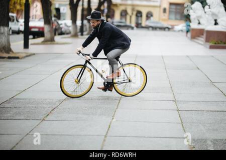 Giovane uomo barbuto Bicicletta Equitazione per lavorare su strada urbana Foto Stock