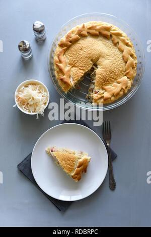 Fetta di crauti fatti in casa torta grigio su un tavolo di legno. Torta cavolo tradizione alimentare russo Foto Stock