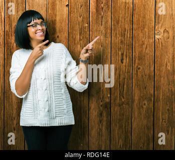 Bella giovane americano africano donna che indossa gli occhiali su sfondo isolato sorridente e guardando la fotocamera con le due mani e dita Foto Stock