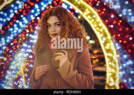 Giovani attraenti i Capelli rossi ragazza. Ritratto sulla strada notte della città. Bokeh da luci festose.