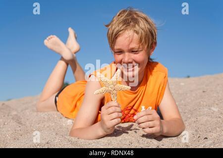 Ritratto di un giovane ragazzo con una stella di mare essiccata su una spiaggia Foto Stock