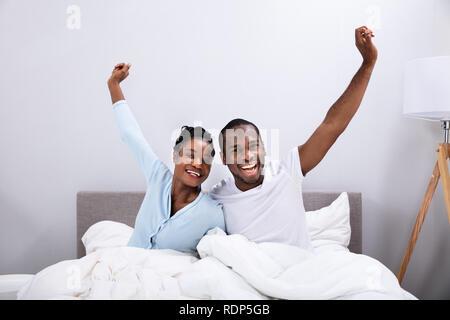 Ritratto di un felice giovane africano giovane alzando le braccia sul letto Foto Stock