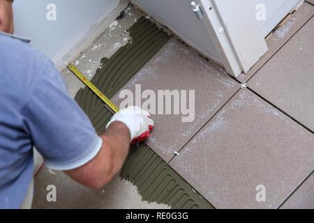 Il builder misure il pavimento con un cucchiaio per organizzare la