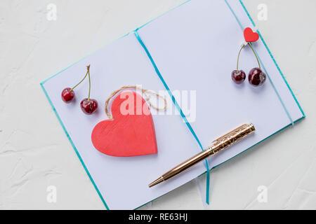 Cuori e ciliegia. Sognando il tema dell'amore. Un quaderno è su sfondo bianco.legno cuore rosso, una dichiarazione di amore. Penna d'oro.Concetto di motivazione in un grazioso ambiente romantico Foto Stock