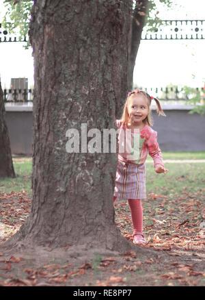 Felice bambina di giocare a nascondino nel parco della città Foto Stock