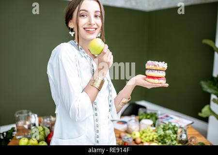 Giovane donna nutrizionista cercando su apple scegliendo tra il cibo sano e dessert