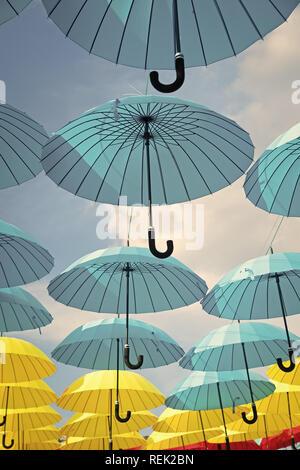 Arte outdoor design e il decor. Ombrelloni galleggiante nel cielo sulla giornata di sole. Ombrello sky progetto di installazione. Vacanza e celebrazione del festival. Ombra e protezione.
