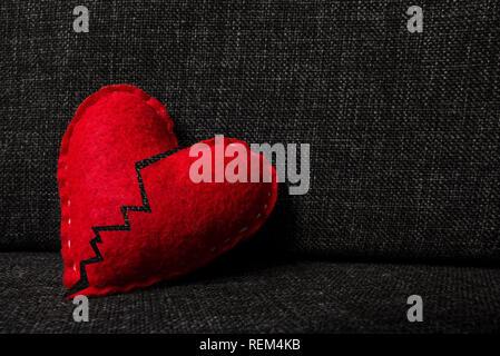 Rosso rotto il giorno di san valentino cuore fatti di lana sul tessuto scuro dello sfondo. Diviso in due parti. Concetto di heartbrake, fine del rapporto e del divorzio.