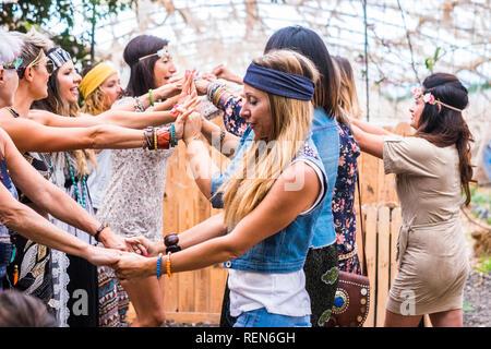 Gruppo di libera e ribelle hippy stile alternativo di donne giovani insieme per ballare e celebrare con gioia e felicità in un luogo naturale indoor e outd Foto Stock