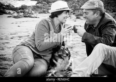 Immagine in bianco e nero con coppia felice in amano sedersi e godersi le attività per il tempo libero outdoor bere insieme con una bella Border Collie cane a metà Foto Stock