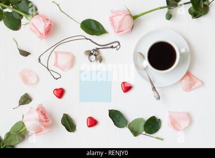 Romantico ancora in vita - la tazza di caffè, peach roses, foglio blu di nota, il gufo orologio a forma di cuore, caramelle sagomata su sfondo bianco. Piatto, laici vista superiore Foto Stock