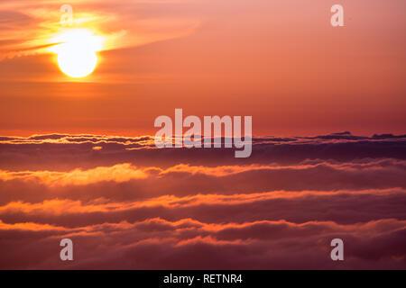 La luminosa luce del sole riflessa su un mare di nuvole prima del tramonto Foto Stock
