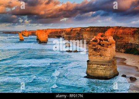 Calda luce del sole al tramonto sulle rocce calcaree formando dodici apostoli nel famoso parco marino di Great Ocean Road in Victoria, Australia. Foto Stock