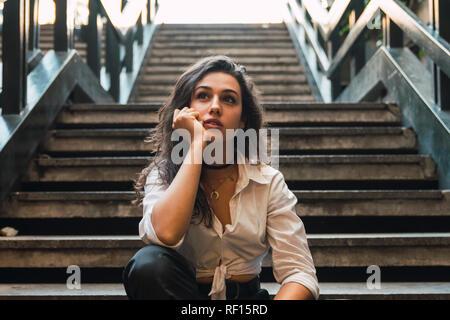 Ritratto di giovane donna seduta sulle scale Foto Stock