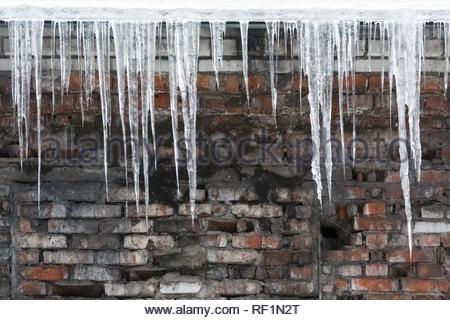 Ghiaccioli pendenti dal tetto dell'edificio, l'acqua gocciola dalle loro copia/spazio/caduta ghiaccioli,riscaldamento improvviso,сold inverno, scarso isolamento termico. Foto Stock
