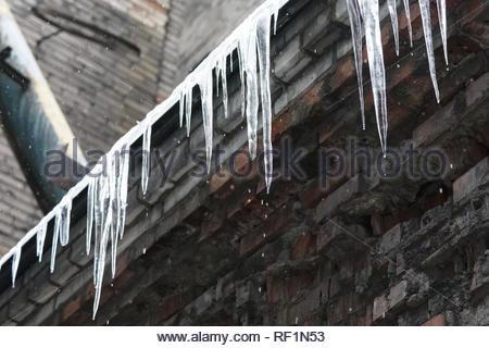 Ghiaccioli pendenti dal tetto dell'edificio, l'acqua gocciola dalle loro/ cadere ghiaccioli, repentino riscaldamento invernale сold, scarso isolamento termico, stalattiti di ghiaccio. Foto Stock