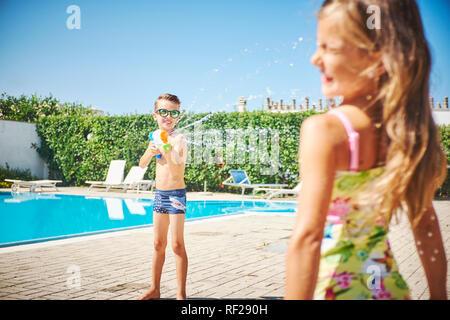 Ragazzo con pistola ad acqua schizzi a ragazza a bordo piscina Foto Stock