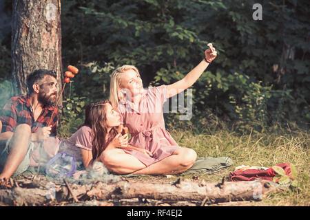 Picnic estivo nel bosco. Sorridente ragazza bionda tenendo selfie nella foresta o parco. Allegro amici in posa con salsicce per foto