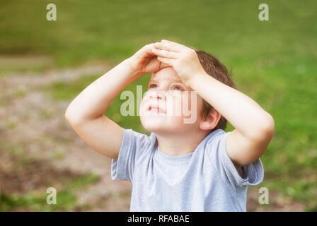 5 anni vecchio ragazzo guarda il cielo che copre la sua gli occhi dal sole con le sue palme Foto Stock