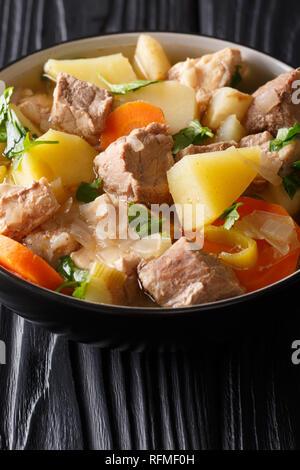 Tedesco Pihelsteiner stufato di carne con verdure e tre tipi di carni di close-up in una ciotola sul piano verticale. Foto Stock
