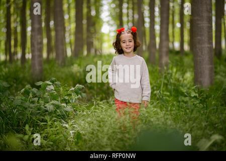 Carino bambina di quattro anni per divertirsi in un bosco di pioppo Foto Stock