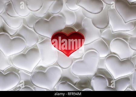 Rosso cuore tessili su bianco cuori sfondo. Il giorno di San Valentino la texture e il concetto di amore Foto Stock