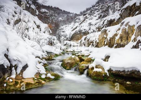 I colori vivaci di una mountain creek cascading attraverso il canyon coperto di neve Foto Stock