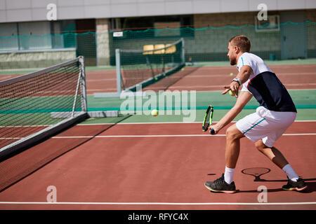 Giovane sportwear sta giocando a tennis su porta di corte. Foto Stock