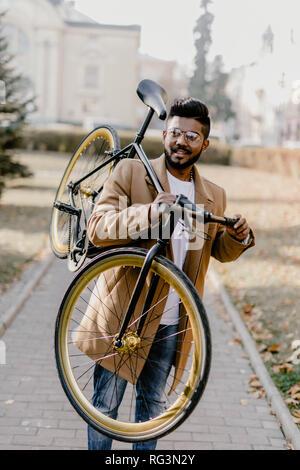 b76618ea82fa96 ... Indiano barbuto hipster uomo con una fixie bicicletta. Basso angolo di  vista fiducioso giovane uomo