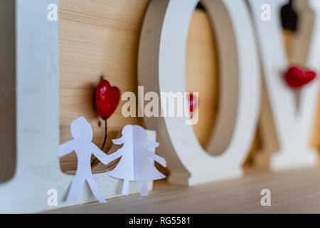 Isolato di carta origami un ragazzo e una ragazza tenendo le mani con un cuore rosso tra loro e la parola 'amore' dietro con sfondo di legno - Concetto di amore, H Foto Stock