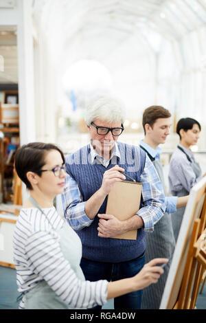 Ritratto di maturo maestro d'arte aiutando un gruppo di studenti Foto di pittura su cavalletto in classe d'arte