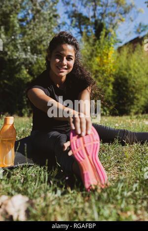 Sporty giovane donna stretching la gamba su un prato Foto Stock