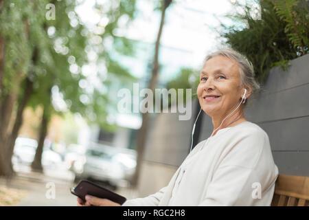 Senior sorridente donna seduta su una panchina all'aperto con un telefono cellulare e auricolari Foto Stock