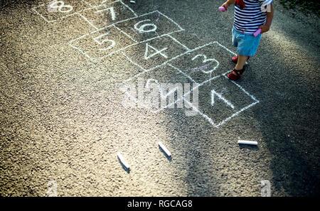 Bambina con tratte campana sulla strada, vista parziale Foto Stock